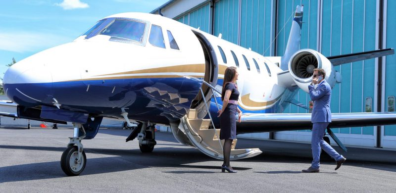 Young man having a call while embarking on executive jet